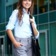 Portrait of a beautiful young businesswoman with briefcase, back - Stock Photo