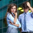 Young worry bussinesswoman and bussinessman in blue shirts, back — Stock Photo #14251351