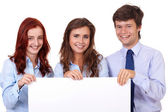 Two businesswomen with businessman holding white board, isolated — Stock Photo