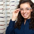 Young woman at optician with glasses, background in optician sho — Stok fotoğraf