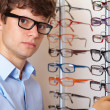 Young man at optician with glasses, background in optician shop - Stock Photo