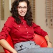 Стоковое фото: Young woman at optician with glasses, background in optician sho