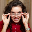 Young woman at optician with glasses, background in optician sho - Stock Photo