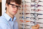 Young man at optician with glasses, background in optician shop — Stock Photo