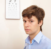 Attractive young man with an eye chart behind — Stock fotografie