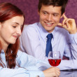 Young happy couple with wineglass in a restaurant, background — Stock Photo