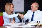 Young businesswoman shake hands with senior businessman, backgro — Stock Photo