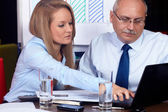 Young businesswoman discuss with senior businessman, background — Stock Photo