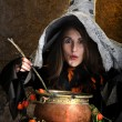 Witch cooking in a copper cauldron — Stock Photo
