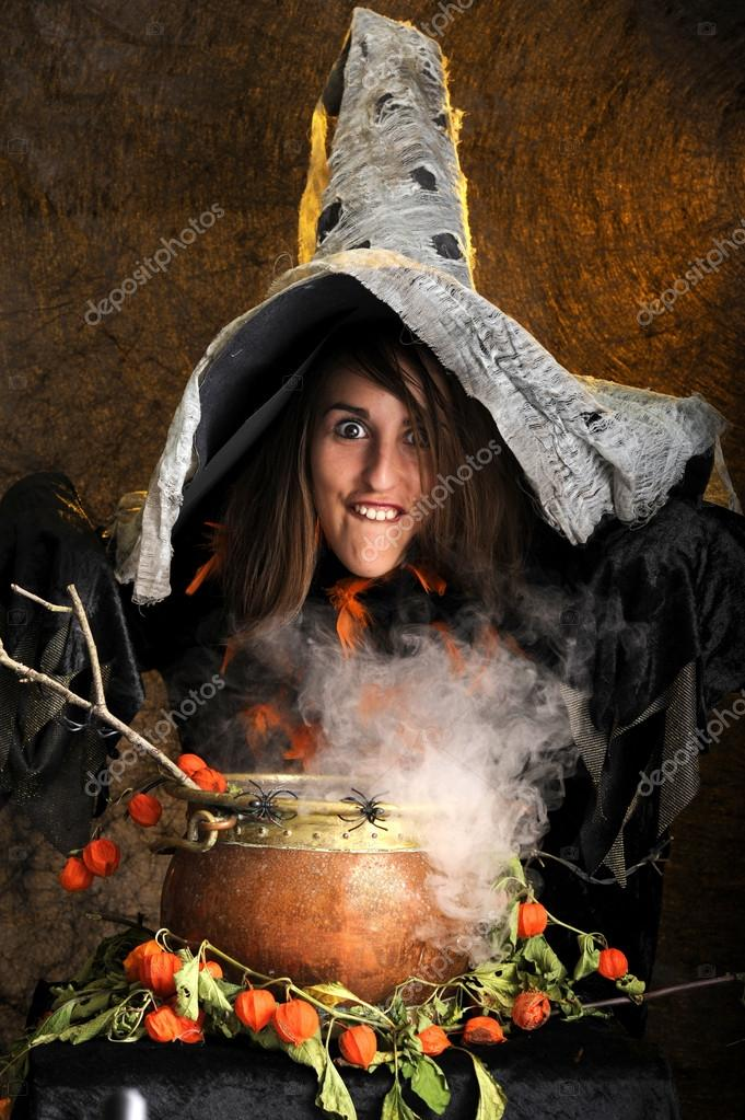 Witch making faces and cooking in a copper couldron — Stock Photo #12440293