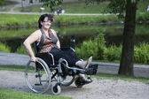 Adult woman in wheelchair outdoors in the park — Stock Photo