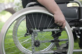 Closeup on hand and wheelchair — Stock Photo