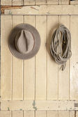 Leather cowboy hat hanging on an old door — Stock Photo