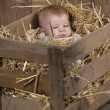 Baby in crate with straw — Stock Photo
