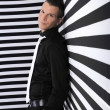 Handsome young man against striped black and white background — Stock Photo