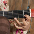 Closeup on a child's hand playing the guitar — Stock Photo