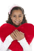 Girl holding a heart shaped pillow in her arms — Stock Photo