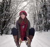 Young woman doing a sledge sliding on a winter road — Stok fotoğraf