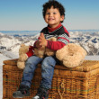 Stock Photo: Little boy seated on big basket