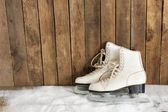 Ice skates against an weathered wooden wall — Stock Photo