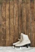 Vecchi pattini da ghiaccio contro una parete di legno stagionato — Foto Stock