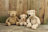 Three teddy bears seated against a wooden wall — Stok fotoğraf