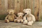Trois ours en peluche assis contre un mur en bois — Photo