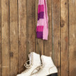 Old ice skates and scarf against an weathered wooden wall - Stock Photo