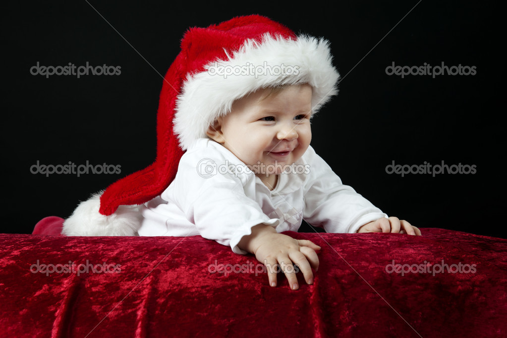 Little baby with christmas hat, lying on her belly, looking up  Stock Photo #15790575