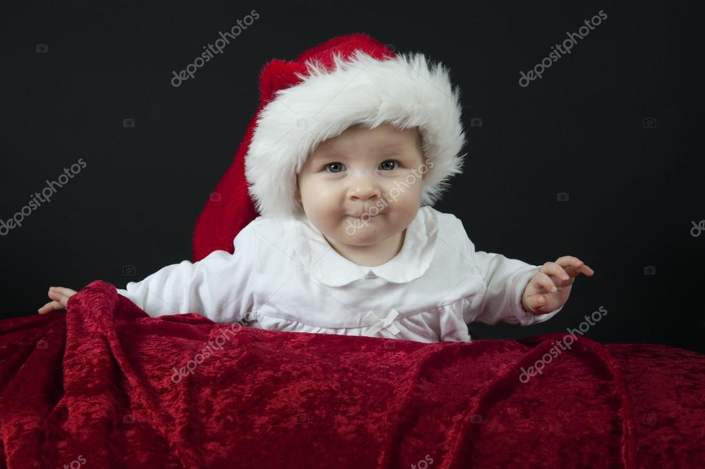 Little baby with christmas hat, lying on her belly  Stock Photo #15790643