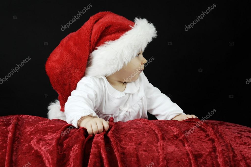 Little baby with christmas hat, lying on her belly, looking up — Stock Photo #15791089