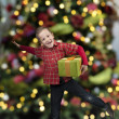 Happy boy with present in front of a christmas tree — Stock Photo