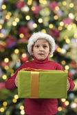 Child with christmas present and hat — Stock Photo