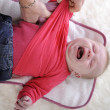 Stock Photo: Crying baby being undressed