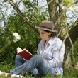Woman reading a book under a tree in the garden — Stock Photo
