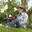 Woman reading a book under a tree — Stock Photo