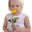 Little girl in white smelling yellow rose — Stock Photo