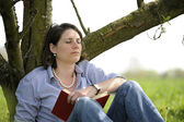 Woman resting under a tree — Stock Photo