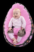 Laughing baby girl in lying in an egg shaped chair — Stock Photo