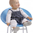 Cute little baby girl sitting in a chair - Stock fotografie
