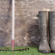 Garden boots and rake on grass against a wooden wall — Stock Photo #21173215