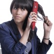 Young woman with hair straightener — Stock Photo