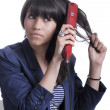 Stock Photo: Young womwith hair straightener