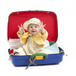Baby girl seated in a suitcase on white — Stock Photo