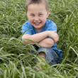 Young boy seated in meadow — Stock Photo