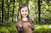 Child in leopard costume in the wood — Stockfoto