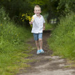 Stock Photo: Mother's day : little boy with flowers , outdoors