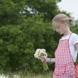 Girl with apron and bouquet of daisies outdoors — Stock Photo