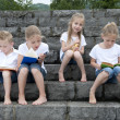 Summer holidays: children with a book seated outdoors on stairs — Stock Photo