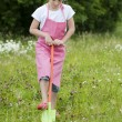 Gardening: girl with rake, outdoors — Stock Photo